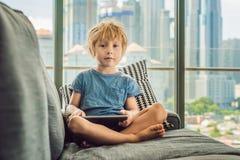 男孩在一个窗口的背景在家使用一种片剂在长沙发与摩天大楼的 现代孩子在特大的城市使用ta 库存图片