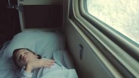 男孩在一列移动的火车清早,面孔特写镜头的汽车睡觉 影视素材