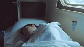 男孩在一列移动的火车的汽车睡觉在晚上 影视素材