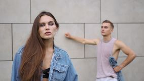 男孩在一名诱人的妇女后的桃红色衬衣立场穿戴了牛仔裤夹克的 股票视频