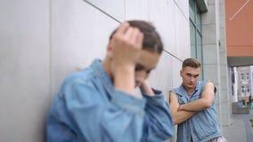 男孩在一名诱人的妇女后的桃红色衬衣立场穿戴了牛仔裤夹克的 影视素材