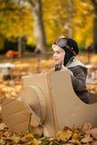 年轻男孩在一架纸飞机的秋天公园 免版税库存图片