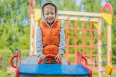 男孩在一辆木汽车站立在操场 免版税库存照片