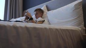 男孩在与一个智能手机的床上说谎在他的手上 通信和比赛在智能手机 影视素材