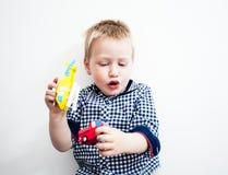 男孩在与玩具的地板上说谎 免版税库存照片