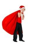 男孩在与红色礼品袋子的圣诞老人帽子 库存图片