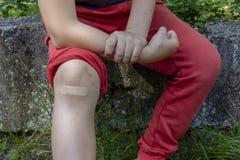 男孩在与绷带的痛苦中在他的膝盖 免版税库存图片