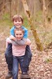 给男孩在乡下步行的女孩肩扛乘驾 库存照片