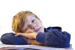 男孩在书倾斜了他的手肘 一只眼睛是开放的 免版税库存照片