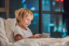 男孩在他的床在夜城市的背景使用片剂在去前睡 孩子和技术概念 免版税库存照片