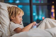 男孩在他的床在ba使用片剂在去前睡 免版税库存图片
