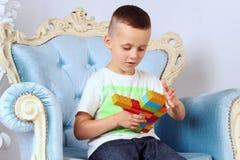 男孩在他的手上拿着一个玩具 免版税库存照片