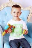 男孩在他的手上拿着一个玩具 库存照片