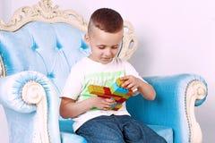 男孩在他的手上拿着一个玩具 库存图片