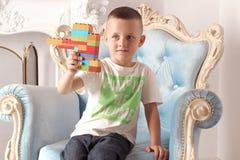 男孩在他的手上拿着一个玩具 免版税库存图片