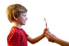 男孩在他的手上拿着一把牙刷 查出 免版税库存照片