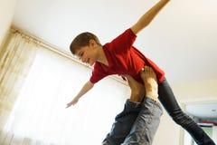 男孩在他的父亲的腿描述有被伸出的胳膊的一架飞机,支持 免版税库存照片