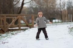 男孩在使用在雪的公园 库存图片