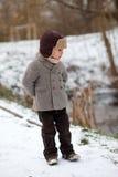 男孩在使用在雪的公园 免版税库存图片