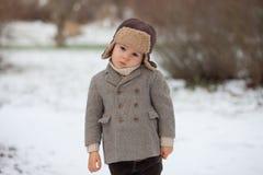 男孩在使用在雪的公园 免版税库存照片