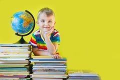 男孩在儿童` s书和地球旁边坐 绿色B 免版税库存照片