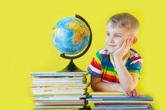 男孩在儿童` s书和地球旁边坐 绿色B 免版税库存图片