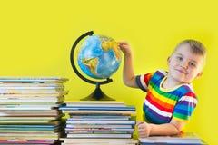男孩在儿童` s书和地球旁边坐 绿色B 免版税图库摄影
