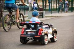 男孩在公园乘坐一辆玩具汽车 免版税库存照片