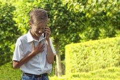 男孩在公园情感地讲话由电话 库存照片