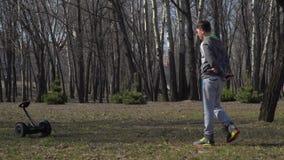 男孩在公园走并且推挤在他自己前面的陀螺仪 影视素材