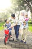 男孩在公园骑有家庭的自行车 免版税库存图片