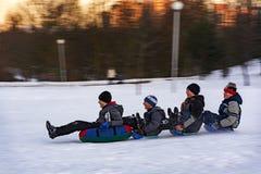 男孩在冬天sl滚动下来倾斜多雪的山 库存图片