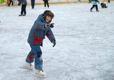 男孩在冰学会滑冰 免版税库存图片