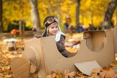 年轻男孩在厚纸飞机的秋天公园 免版税库存图片