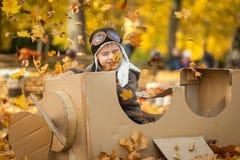 年轻男孩在厚纸飞机的秋天公园 库存图片