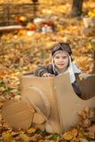 年轻男孩在厚纸飞机的秋天公园 免版税库存照片
