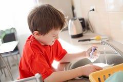 男孩在厨房里洗盘子 图库摄影