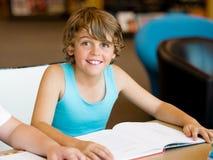 男孩在图书馆里 免版税图库摄影