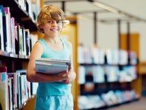 男孩在图书馆里 库存照片