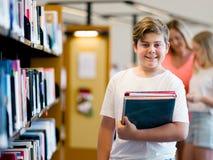 男孩在图书馆里 图库摄影