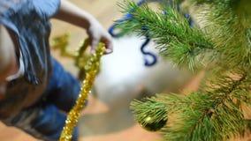 男孩在圣诞树上装饰家里的玩具 影视素材