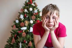 男孩在圣诞树附近在他的手上坐他的头 库存图片