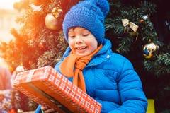 男孩在圣诞节市场上的树前面与礼物 免版税库存照片