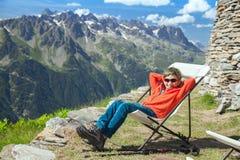 男孩在夏天山的一张轻便折叠躺椅休息 免版税图库摄影