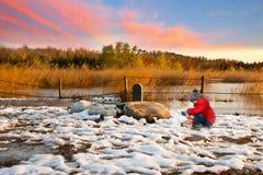 男孩在多雪的妙境演奏他的玩具汽车 免版税库存照片