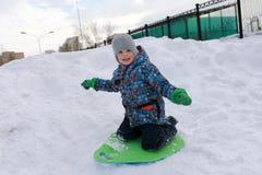 男孩在多雪的小山滑 免版税图库摄影