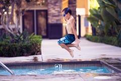 男孩在天空中,跳跃在水池 免版税库存图片