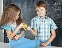 男孩在学校给女孩一个苹果 库存图片