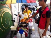 男孩在安蒂波洛买kwek-kwek从一个街道食品厂家的一个地方纤巧 免版税库存图片