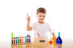 男孩在实验室里混合化学制品 免版税库存照片